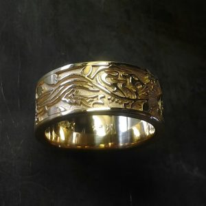 custom gold wedding band with leaf and vine engraving