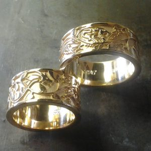 matching custom gold wedding bands with leaf and vine engraving