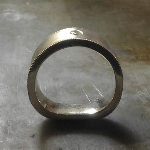 custom wedding band with solitary round diamond side view