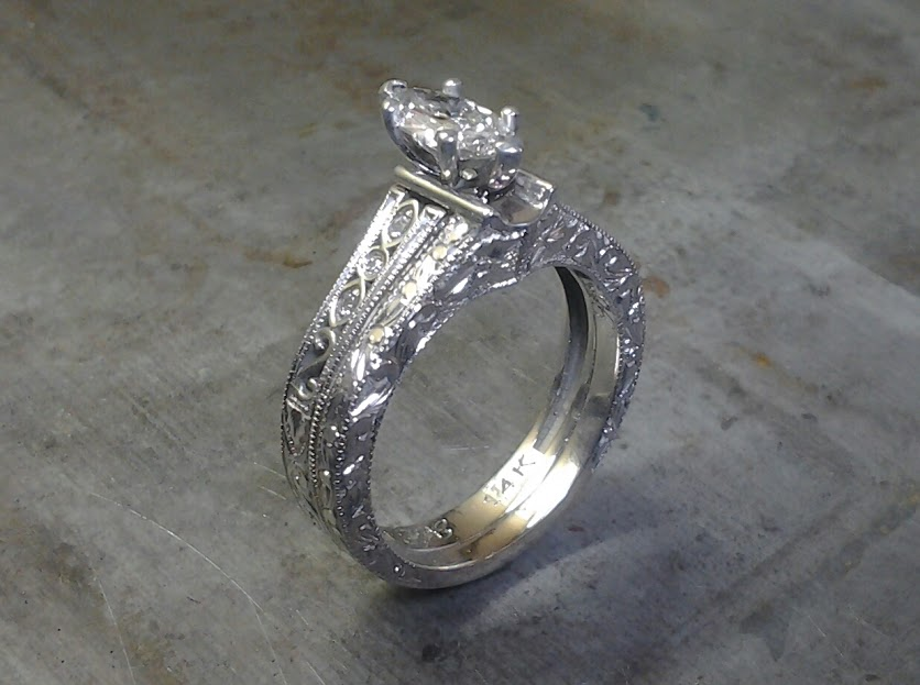 intricate filigree band with marquise center stone in a cathedral setting side view