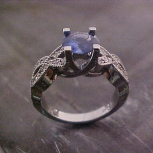 white gold ring with woven band and sapphire