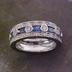 custom band with sapphires and round diamonds in bezel setting