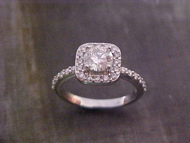 diamond encrusted engagement ring with round diamond in square halo setting