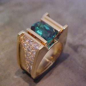custom ring with gold and diamond band and large center emerald