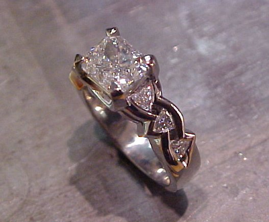 triangle diamond accents and large radiant diamond center stone in gold engagement ring