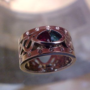 custom white gold ring with celtic engraving and ruby and emerald center gems top view