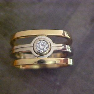 custom wedding ring with yellow and white gold and solitary round diamond top view