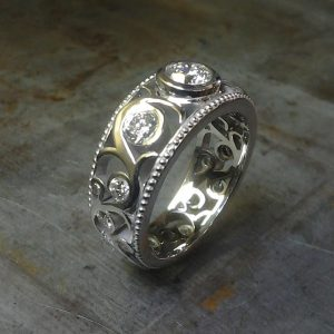 custom swirled band with round bezel set diamonds