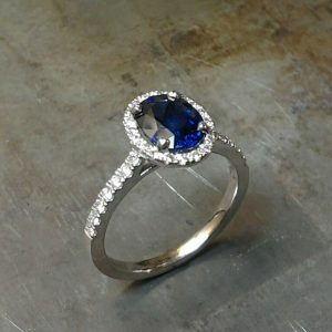 Royal Blue Sapphire set in 19k white gold with diamond set halo and sides