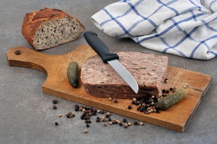 Pâté de campagne sur une planche à découper avec du pain, des cornichons et un mélange de baies