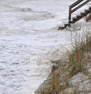 Waves lap against sand dunes south of Sadler Road during previous storm