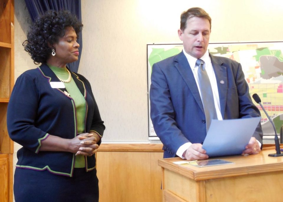 Nassau County Council on Aging Executive Director Janice Ancrum listens to Mayor John Miller recognize her organization's efforts on behalf of senior citizens.