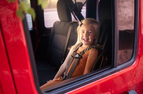 Toddler girl sitting in WAYB Pico Kids Travel Car Seat in red Jeep Rubicon