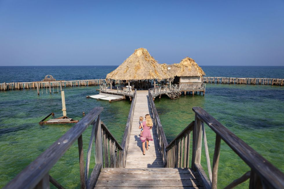 Mother and baby walking on dock towards a thatched bungalow hut over the ocean