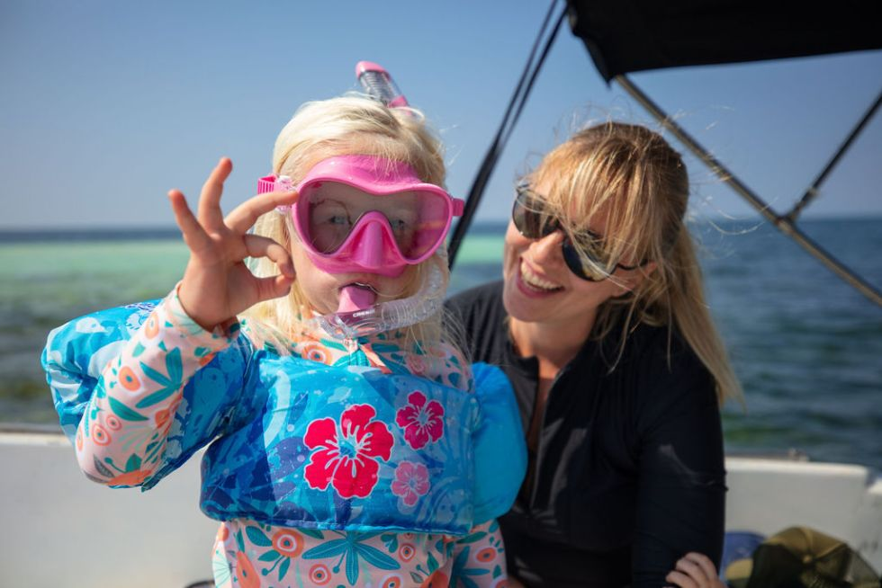 """Mother and daughter preparing to go snorkeling, daughter giving """"okay"""" Scuba sign with her fingers"""