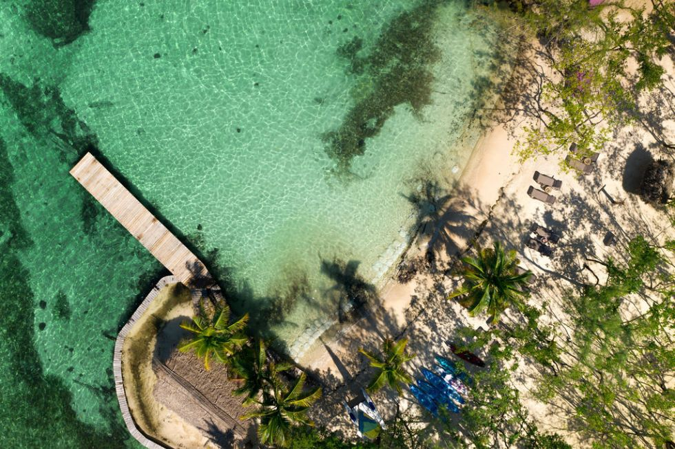 Aerial drone photo of the beach and dock at Thatch Caye island in Belize