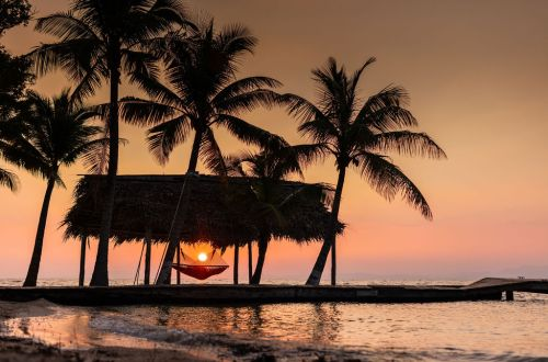 Beautiful orange and pink sunset sky behind palm trees, thatched hut, and dock going out into the ocean