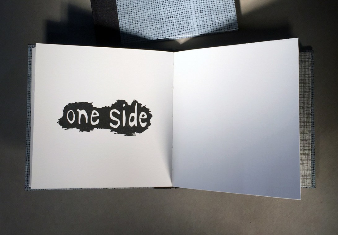 "Interior page of an artist book titled ""1 over 1"", text says ""one side"""