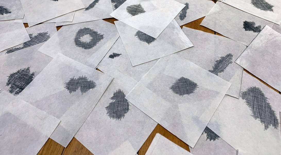 image showing squares of paper printed with an image of torn cloth