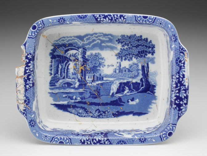 "Paul Scott, ""Cumbrian Blue(s) - Spode Works Closed, Italian Blue, 03/10/09/09l,"" 2013, in-glaze decal, gold lustre on small Spode casserole, (marked Made in Portugal) salvaged from the kiln area in the closed Spode factory 07/09, 3.5 x 9 x 11.25"". Rhode Island School of Design Collection."