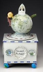 "Mara Superior, ""Smart Planet: Homage to Science"" 2009, porcelain, glaze, wood, gold leaf, tin pencil sharpener (feet), 21 x 17 x 11""."