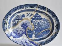 "Paul Scott, ""Scott's Cumbrian Blue(s), Fukushima No: 5,"" 2015, glaze, decal, c. 1965 Japanese Willow platter, brass pins, gold leaf, tile cement, epoxy resin, 14 x 18.75 x 2""."