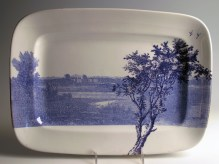 "Paul Scott, ""Cumbrian Blue(s), American Scenery, Hudson River, Indian Point No. 1"" 2013, inglaze decal collage, gold luster on J&G Meakin Ironstone platter c. 1850, 7 x 10"". Brooklyn Museum Collection."