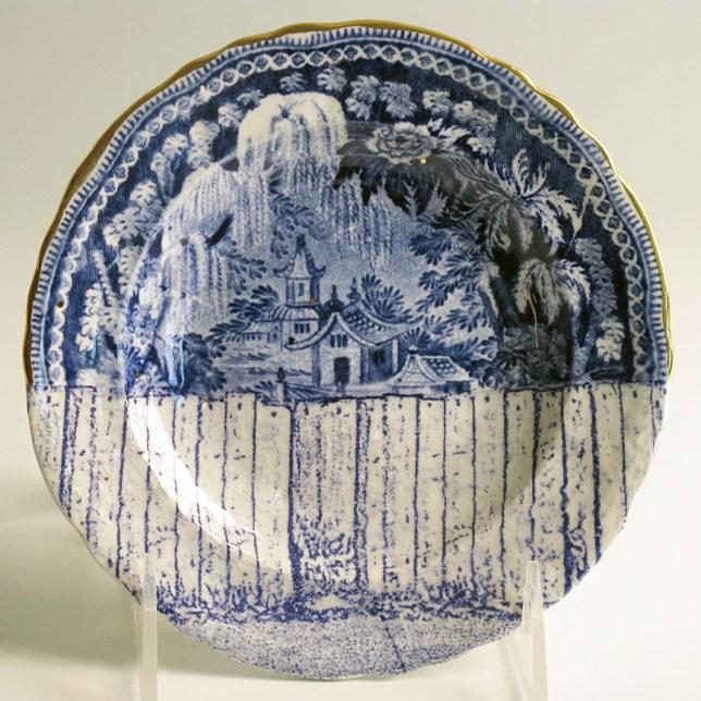 "Paul Scott, ""Cumbrian Blue(s), Scenery, Palestine"" 2013, inglaze decal collage, gold luster on R. Stephenson pearlware plate c. 1830, 6.25 x .5""."