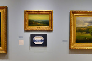 """Mount Holyoke College Art Museum: (right) George Inness, American (1825-1894), """"Saco Ford: Conway Meadows"""" 1876, oil on canvas. (center top) Homer Dodge Martin, American (1836-1897), """"A Glimpse of Lake Placid,"""" 1887, oil on canvas. (center bottom) Paul Scott, """"Scott's Cumbrian Blue(s), American Scenery, Hudson River, Indian Point No. 4, """" 2015, ceramic transfer decal.  (left) Albert Bierstadt, American (1830-1902), """"Hetch Hetchy Canyon,"""" 1875, oil on canvas"""