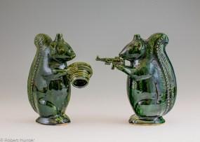 "Michelle Erickson, ""Green Squirrel"" (left), ""Second Amendment Squirrel"" (right), 2013, indigenous clay, glaze, 8""."