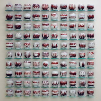 "Steven Young Lee, ""Cup Panels"" (red), 2013, porcelain, copper inlay, glaze, glass shelving, aluminum, 46 x 50 x 4""."