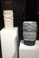 """Andy Brayman, """"Vase with Orange and Blue"""" (left), 2013, porcelain, glaze, decals, 19 x 10 x 7"""". """"Black Vase with Yellow and Green"""" (right), 2013, porcelain, glaze, decals, 17.5 x 10 x 7""""."""