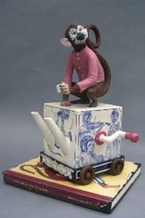"Red Weldon Sandlin, ""The Hurtea Gurdy Tales: A Nickle for the Monkey"" 2006, ceramic, wood, acrylic paint, 16.5 x 11.5 x 11"", book: 1 x 12 x 9"". (Greenspun)"