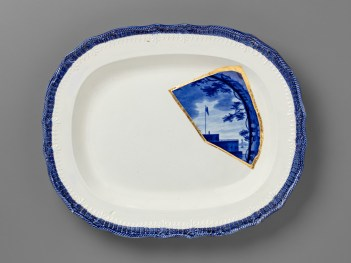 "Paul Scott, ""Scott's Cumbrian Blue(s), New American Scenery, Castle Garden Battery, New York, after Enoch Wood (triptych)"" 2019, Collage, Fragmented Enoch Wood transferware (c.1840) and gold leaf, set in Leeds Pottery shell-edged pearlware platter (c.1840), with kintsugi, 13 x 16 x 1.75""."