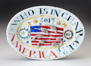 "Mara Superior, ""Who is in Charge, America?"", 2019, high-fired porcelain, ceramic oxides, underglaze, glaze, overglaze enamel, gold leaf, 6.5 x 9.5 x 1''."