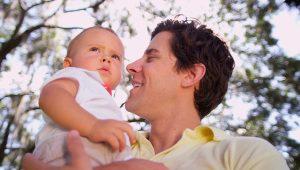 joven padre sosteniendo a su hijo