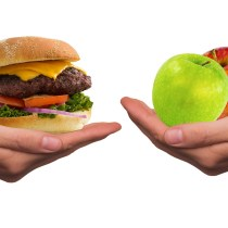 A sinistra un hamburger, a destra della frutta