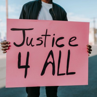 """A man holding a poster that says """"Justice 4 All"""""""