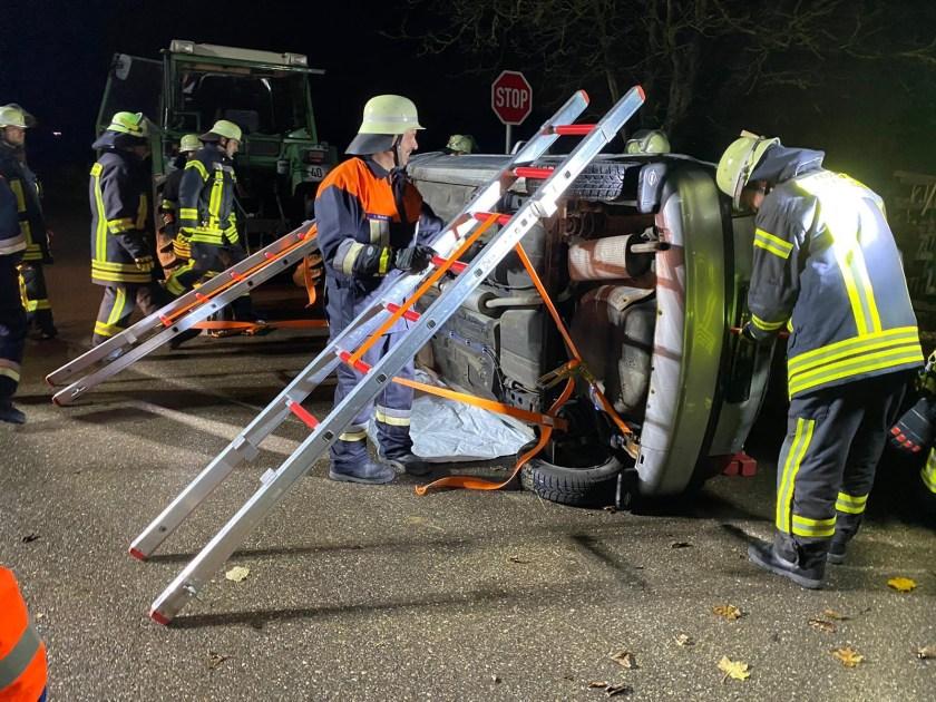 Blick auf das Übungsszenario: Technische Hilfeleistung (THL) bei einem Verkehrsunfall. Übungsobjekt: ein Schrottauto (Opel Corsa) der auf der Seite liegt und mit Leitern und Spanngurten gegen Umfallen gesichert wird.