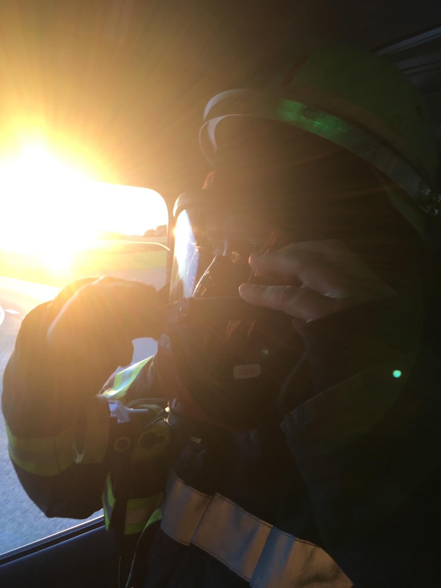 Christian Thoma (1. Kommandant der FF Rieblingen) rüstet sich während der Fahrt mit Atemschutz aus.