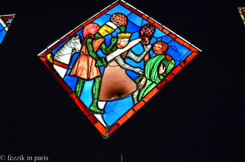 Some stained glass depicting a motherfucker getting cut.