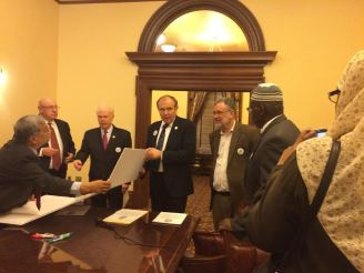 Ali Chaudry hands the Pledge to Sen. Lesniak as Walter Ruby looks on