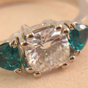 Picture of a custom engagement ring that has green emeralds and a white moisannite stone