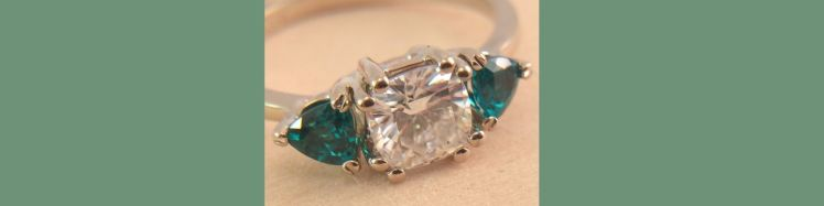 Picture of an engagement ring with green emeralds and a white moissainite stone