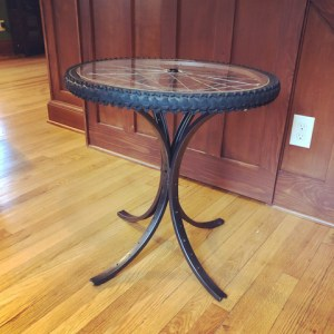 Table with a bicycle wheel and spokes to represent the work of the bike artist who works creates bike chain art