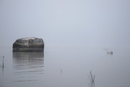 Still rock in the calm foggy lake