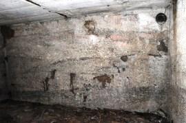 Wand aus Magerbeton. Rechts oben eine von zwei Lüftungsöffnungen.