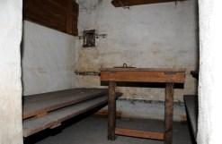 Der Raum war mit Holzpritschen und einem Klapptisch ausgestattet.