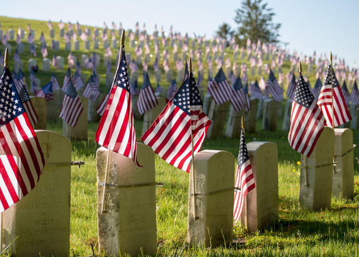 military gravestones with flags.