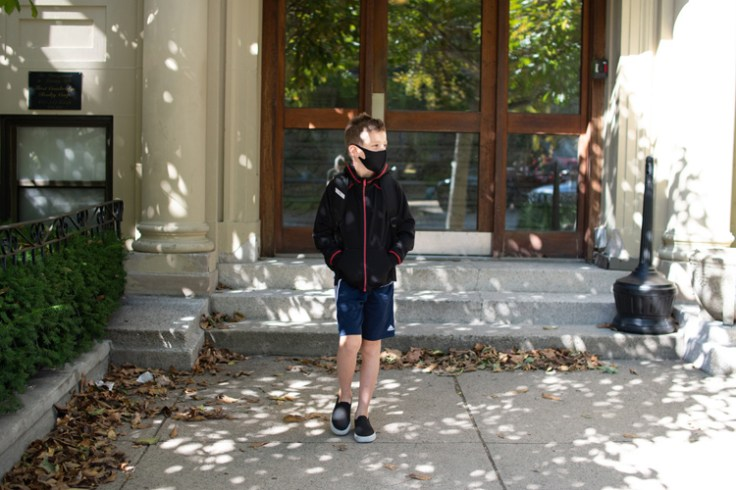 a boy goes to school wearing a face mask.